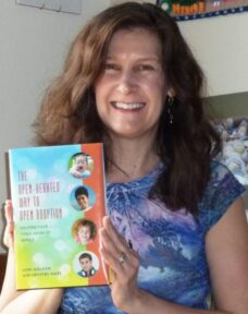 Lori Holden holds a copy of The Open-Hearted Way to Open Adoption