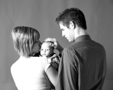 two parents holding a baby